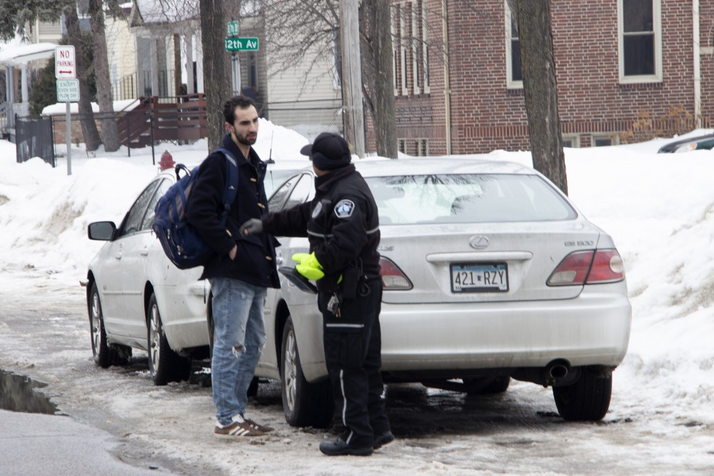 Jose Bonete, a traffic control agent for Minneapolis Regulatory Services, answers questions about where residents of Dinkytown should park to avoid a ticket, on Saturday, March 9, 2019.