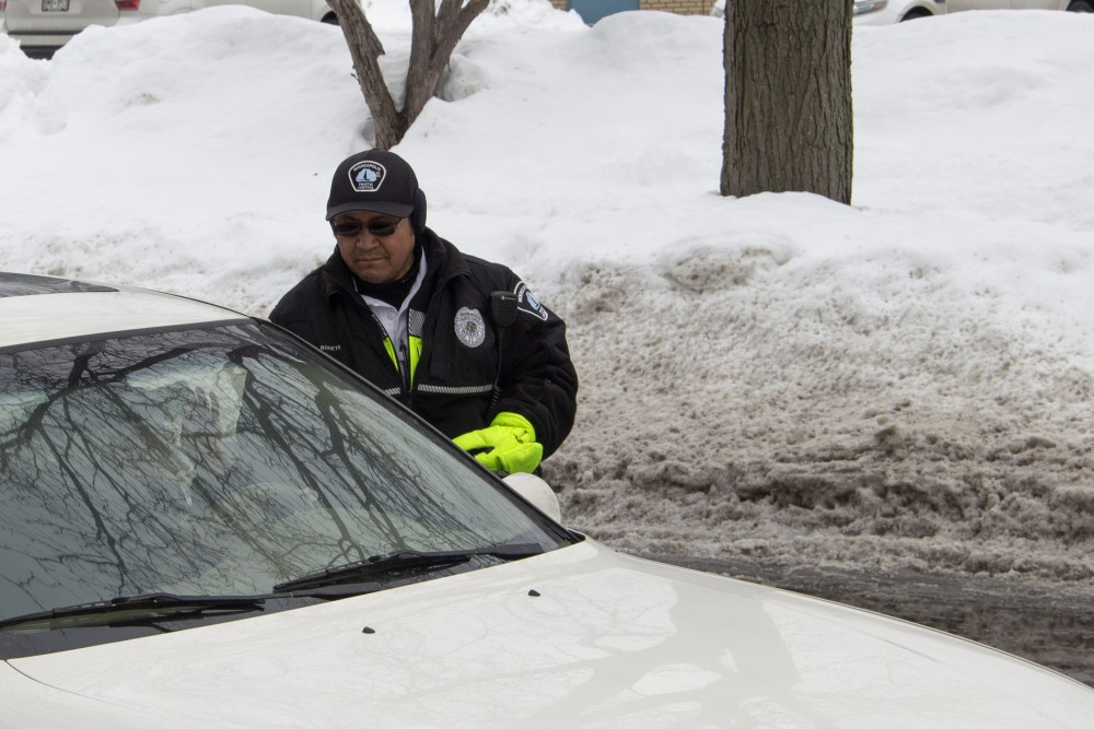 Jose Bonete, a traffic control agent for Minneapolis Regulatory Services, was ticketing vehicles in Dinkytown when University of Minnesota student Julia Hamburger stopped him so she could better understand where to park with the ban in place, on Saturday, March 9, 2019.
