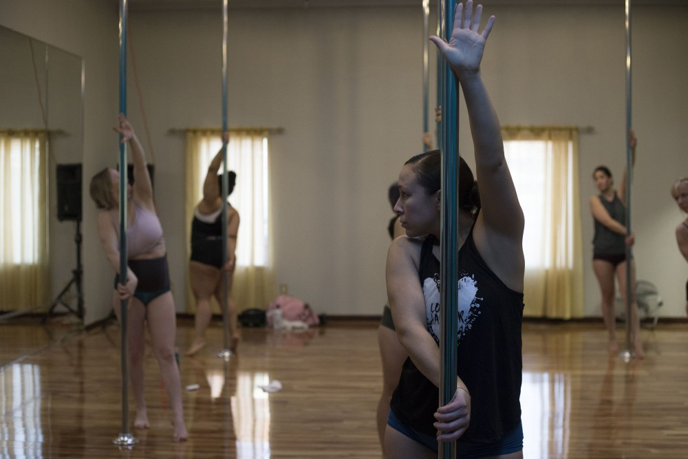 Josie LaChapelle, who has been pole dancing on and off for three years, warms up with the class at Knockout Bodies in Minneapolis on Thursday, March 28.