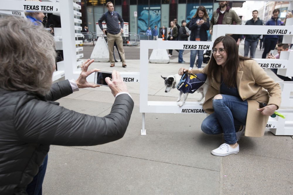Katie Bies poses for a photo with her dog Jerry at the Tip-Off Tailgate on Nicollet Mall on Friday, April 5. Bies, who went to school in Michigan, is rooting for Auburn now that Michigan is out.