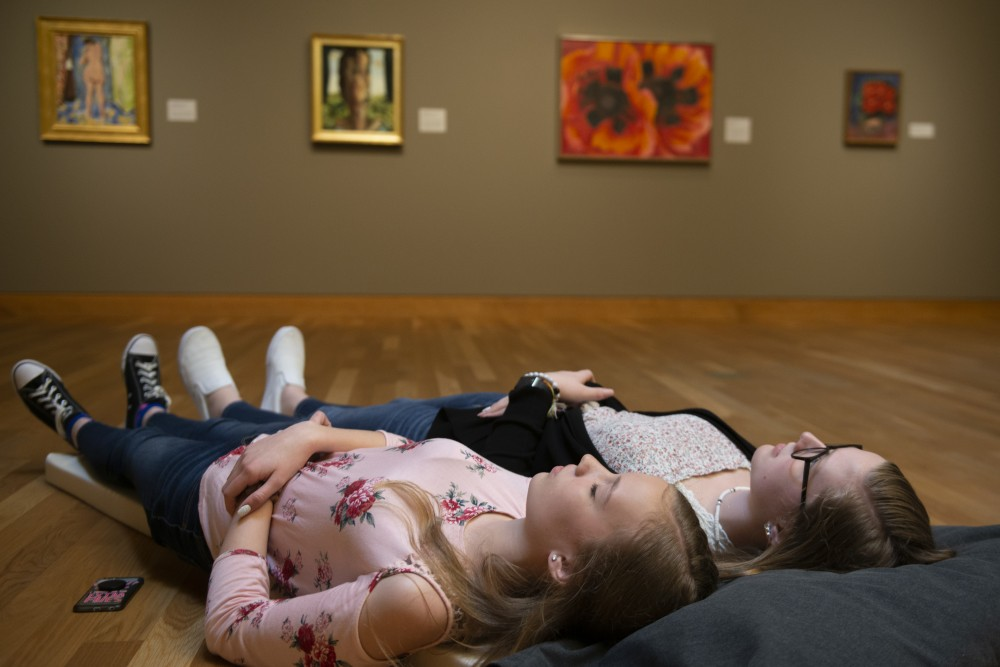 Olivia Danely and Kendra Pockat rest in front of paintings at Slow Art Day at Weisman Art Museum on Saturday, April 6 in Minneapolis. Instead of spending fifteen seconds looking at pieces of art, Slow Art Day asks viewers to take fifteen minutes.