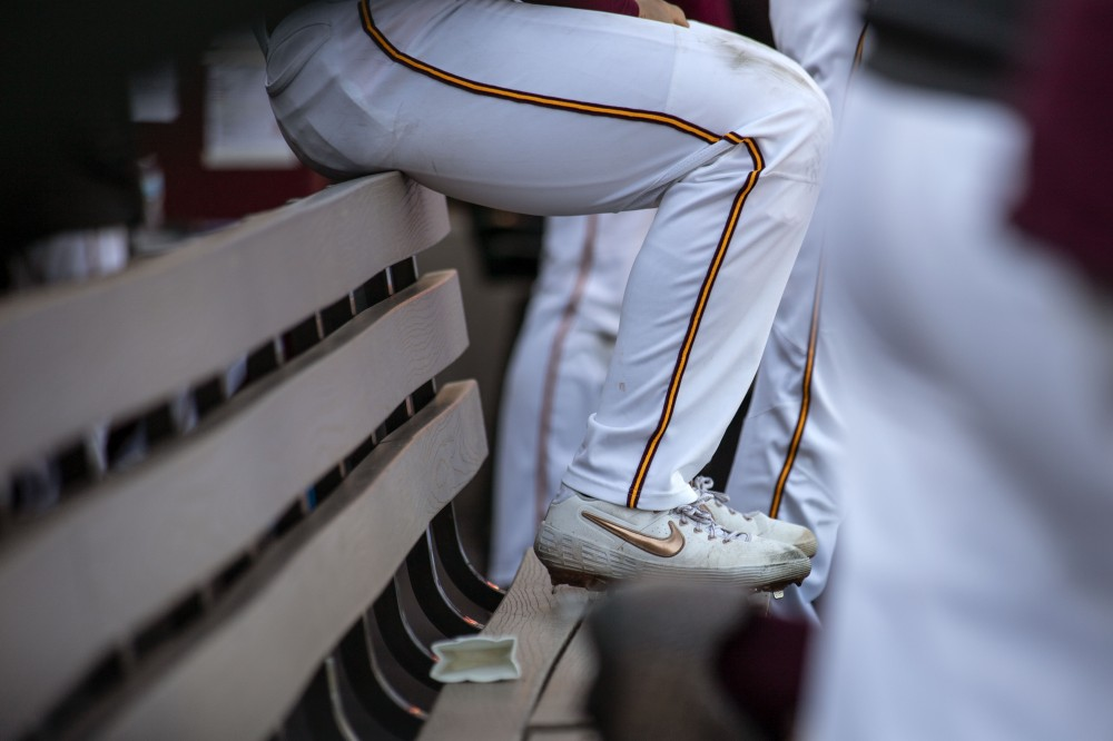 A gopher baseball player sits on the bench on April 14, 2019 at Siebert Field.