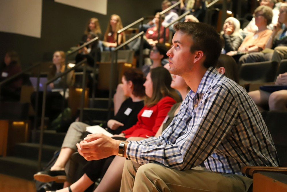 Andrew Rhodes listens in on a presentation about work towards specific climate goals between Minnesota and Germany on Tuesday, April 16 at Northrop Auditorium.