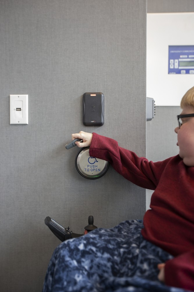 Cole Anderson rests his hand on an automatic push plate so he can reach the sensor for his key fob on Thursday, April 18 inside his apartment building on West Bank. Anderson has Duchenne muscular dystrophy, a genetic, degenerative muscle disease, which makes lifting his arms difficult.