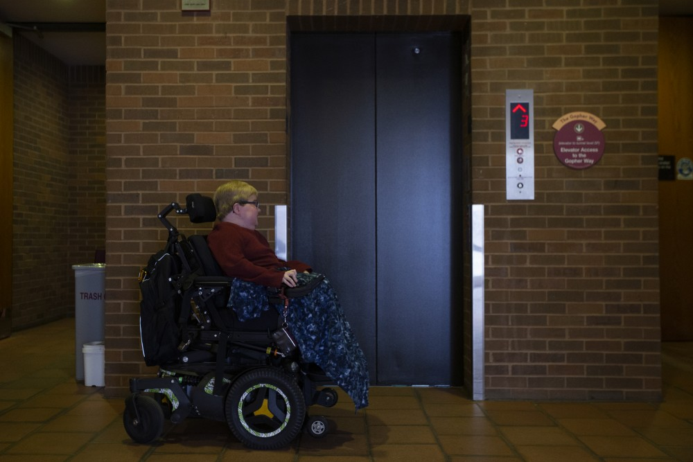 Cole Anderson waits for the elevator in Mondale Hall on his commute to class. From his apartment building to his first class in Blegen Hall, Anderson must use seven elevators. He said reaching to press the elevator buttons makes his arms tired.