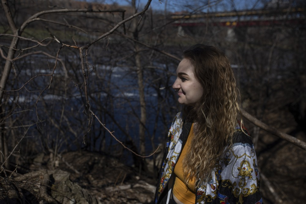 Sophomore Sophie O'Rourke poses for a portrait near the Mississippi River on Friday, April 19. O'Rourke, who has fibromyalgia and identifies as a person with an invisible disability, used the space to decompress after her summer job at Comstock Hall.