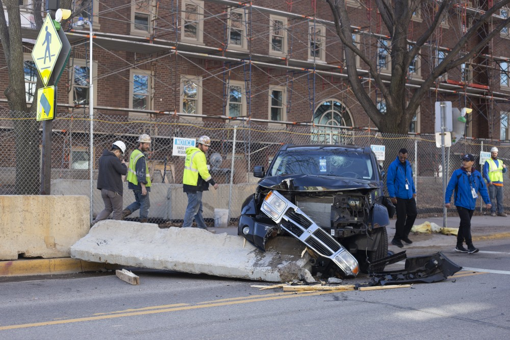 9:39 a.m. Passersby assess the damage from a vehicle crash early in the morning next to Pioneer Hall.