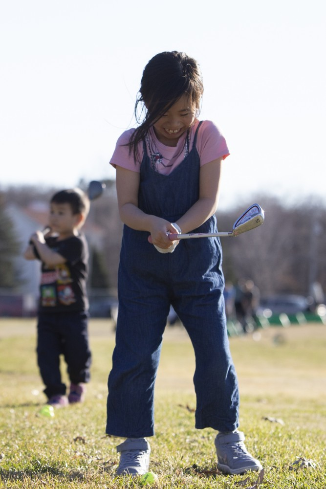 6:19 p.m. Akari Nanno, 7, giggles after missing the golf ball in the foreground as her little brother Haruki Nanno, 3, eyes his shot in the background at the driving range at Les Bolstad Golf Course.