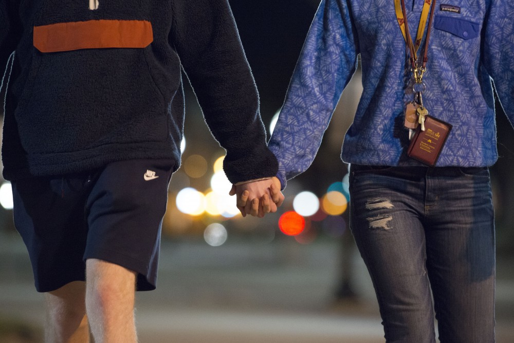 11:37 p.m. Dave De Jong and Marie Lundgren holds hands while walking home after a night of board games.