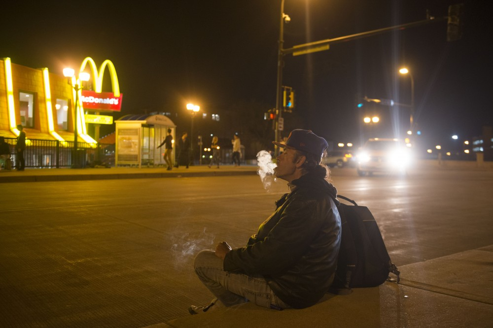 2:15 a.m. Corey Hanson smokes a cigarette across from McDonald's in Dinkytown.