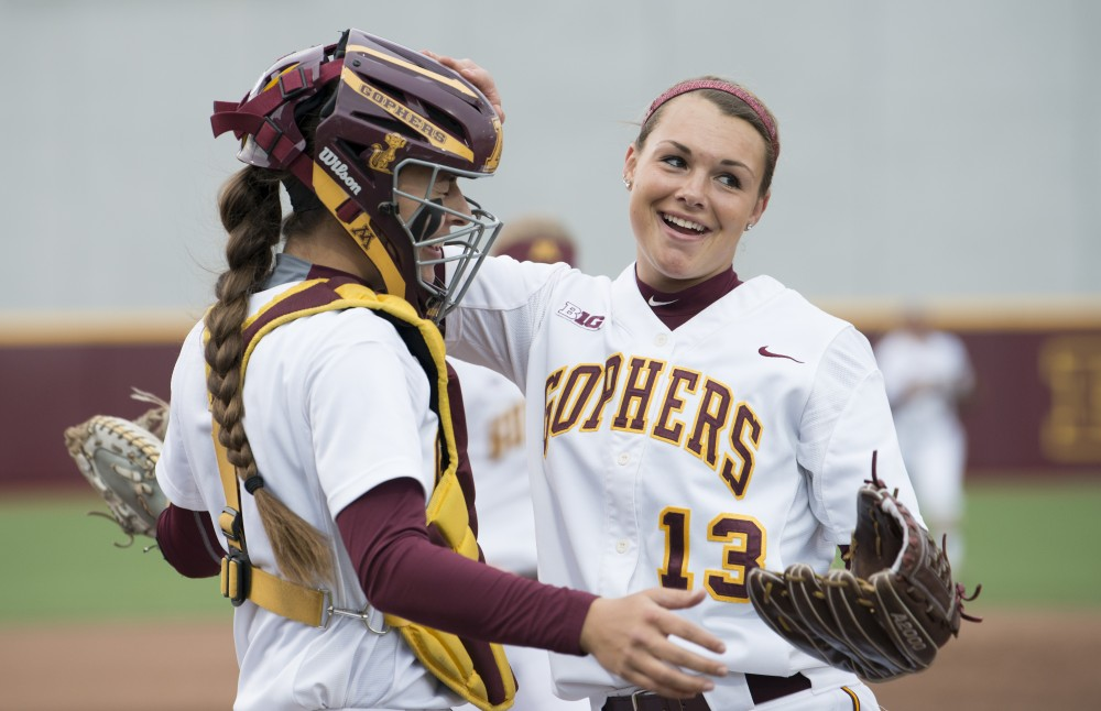 Pitcher Amber Fisher hugs catcher Emma Burns after a strike out pitch at Jane Sage Cowles Stadium against Northwestern on Friday, May 3, 2019.