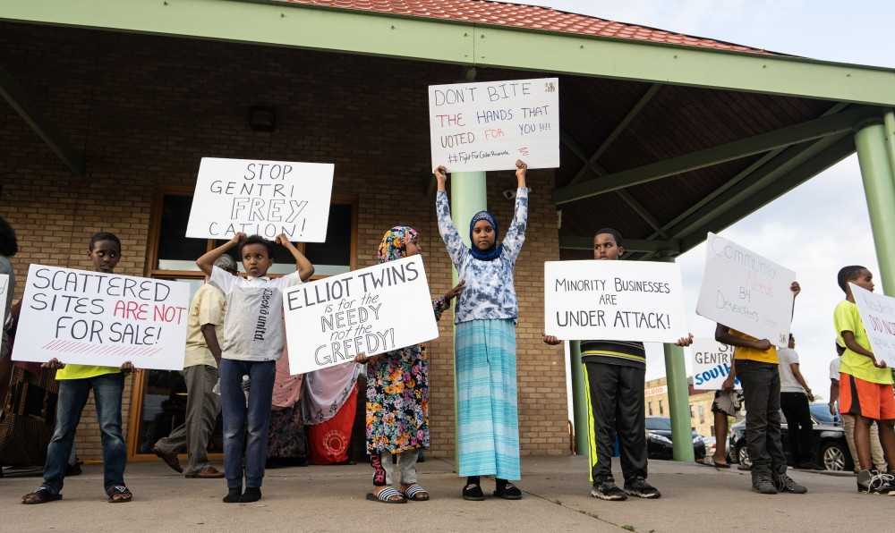 <p>Youth hold signs protesting plans for the development of a mall in the Cedar Riverside area at a protest organized by the Somali Mothers of MN at Currie Park on Sunday, July 7.</p>
