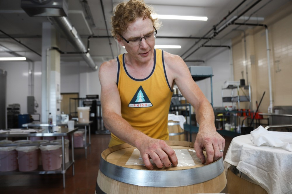 Bryan Deane Bertsch opens a barrel in his kombucha factory on Saturday, July 13 in St. Paul.