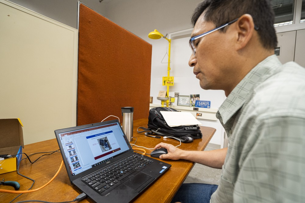 Chen-Fu Liao, a researcher at the Center for Transportation Studies, shows the Bluetooth device for his app designed to help the visually impaired navigate the streets in the Mechanical Engineering building on Wednesday, July 17.