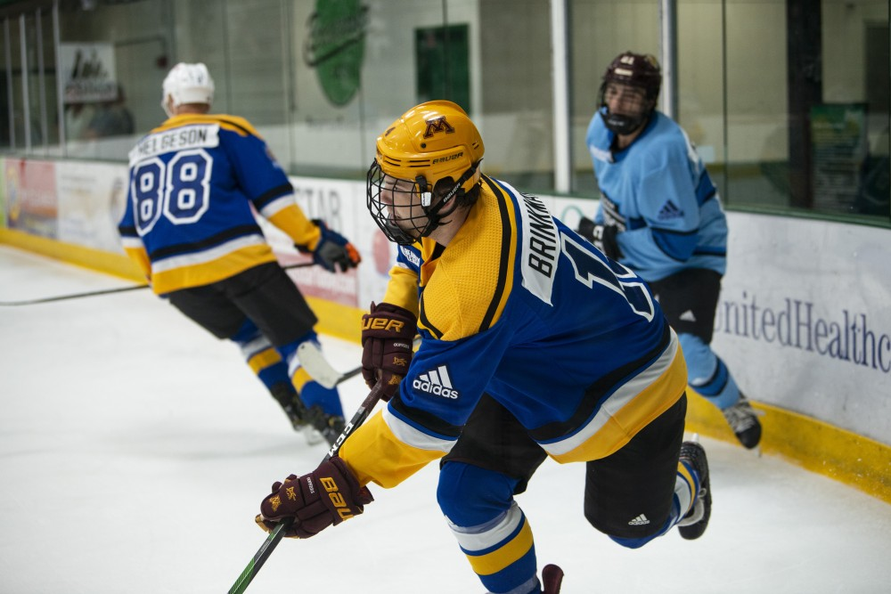 Ben Brinkman keeps the puck away from his opponent in the final game of Da Beauty League at Braemar Arena in Edina on Wednesday, July 18.