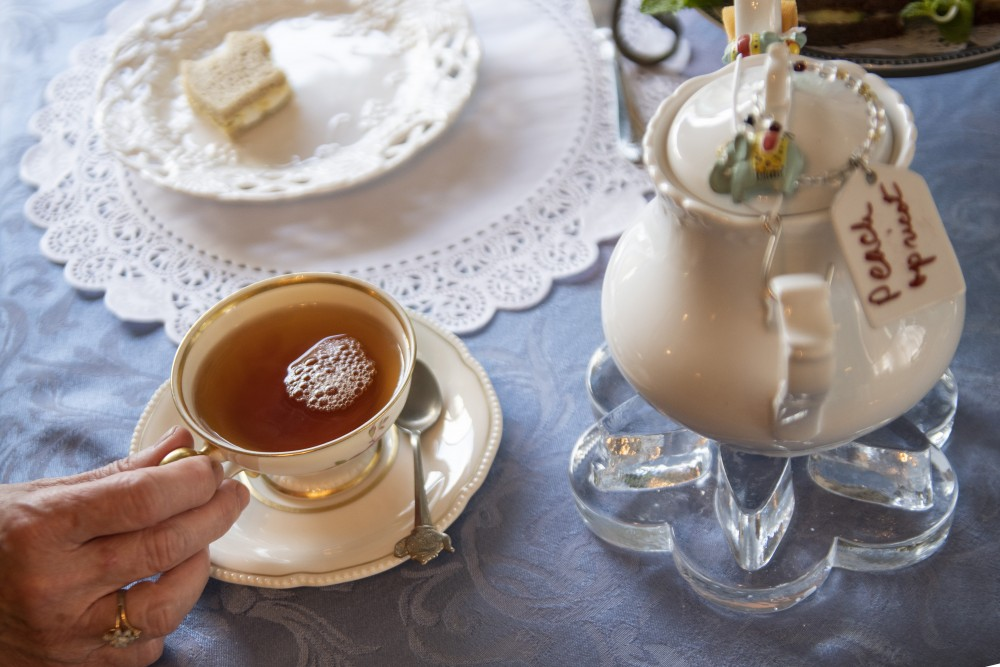 Barbara Haselman reaches for her tea on Wednesday, July 24 at Lady Elegant's Tea Room & Gift Shoppe in St. Paul.