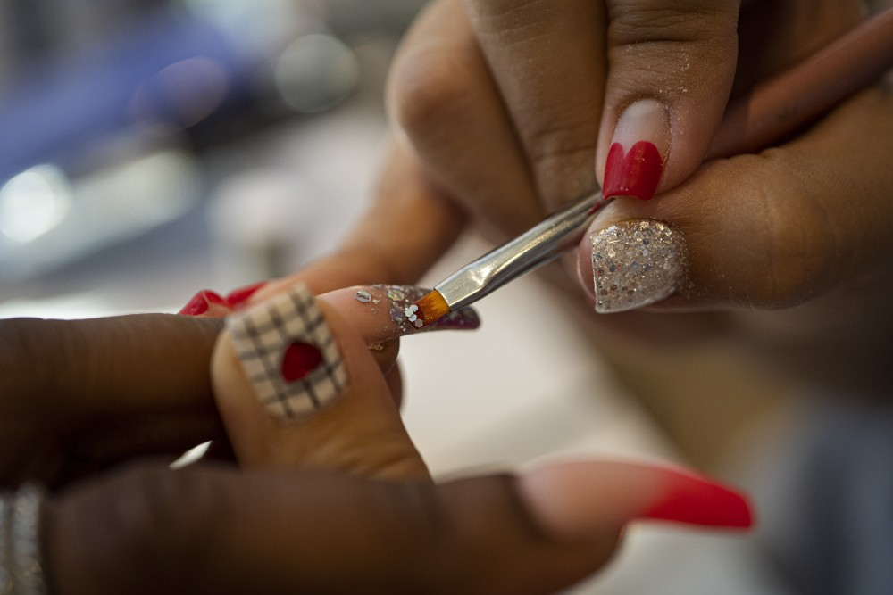 Nail artist Melody Vue paints Jelahn Prentiss' nails at Little Luxuries Nail Lounge in Minneapolis on Tuesday, July 30.