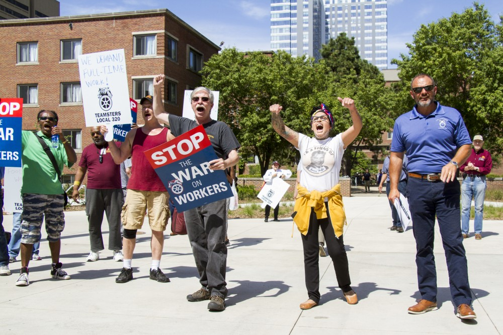Demonstrators from Teamsters Local 320 gather outside Pioneer Hall on Wednesday, Aug. 21. The group said that more than 30 University employees were unfairly laid off over the summer.