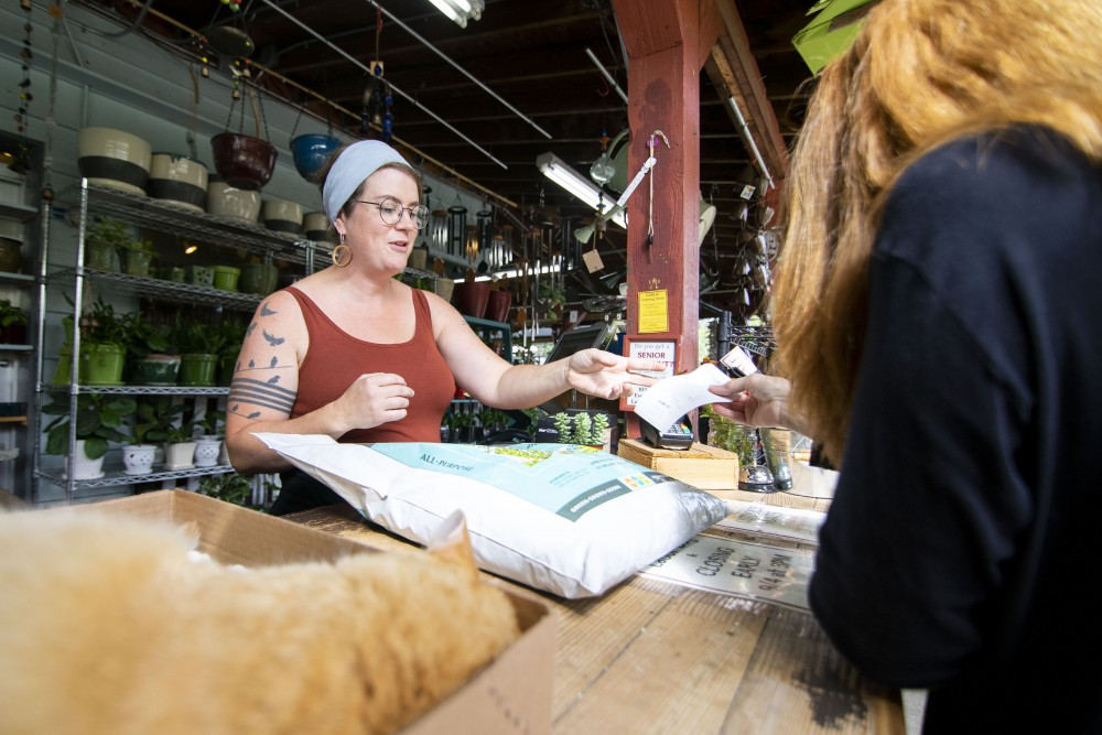 Jessica Langhout-Budge checks out a customer at Mother Earth Gardens on Saturday, Aug. 31.