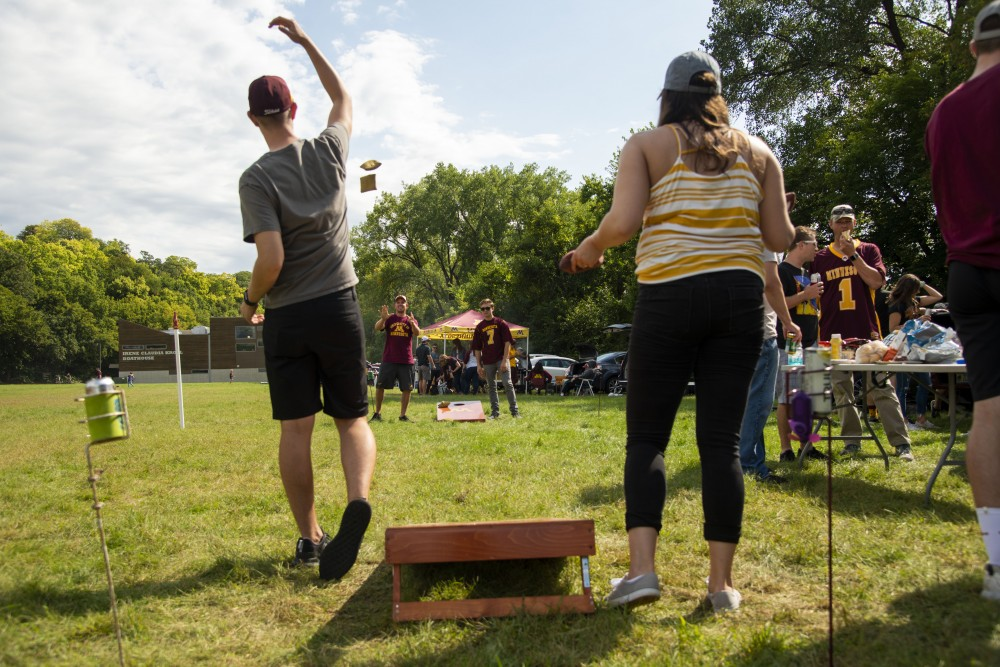 Gopher fans play a game of bag toss at the East River Flats on Saturday, Sept. 14. The Minneapolis Park and Recreation Board is considering disallowing tailgating events such as these on football game days at East River Flats.