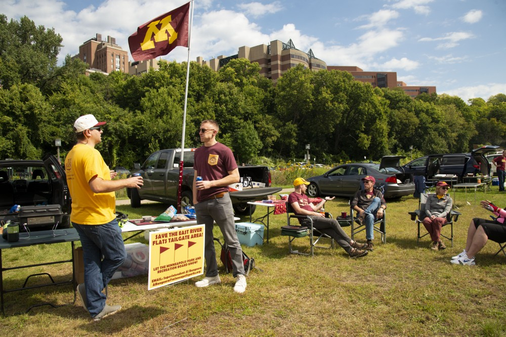 Billy Werb, left, enjoys the company of other alumni at the East River Flats on Saturday, Sept. 14. Werb created signs urging other residents to speak up to the Minneapolis Park and Recreation Board to continue to permit tailgating on football game days.