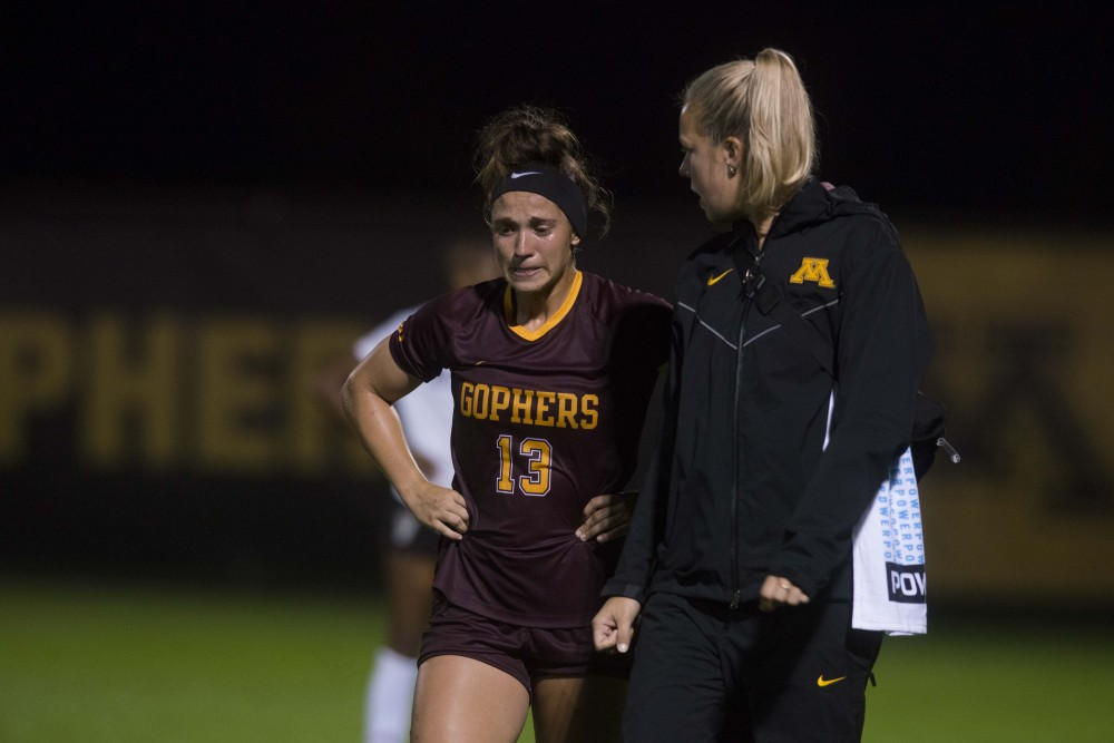 Defender Nikki Albrecht talks to her coach on the sidelines at Elizabeth Lyle Robbie Stadium on Thursday, Sept. 12. The Gophers defeated North Carolina State 1-0.