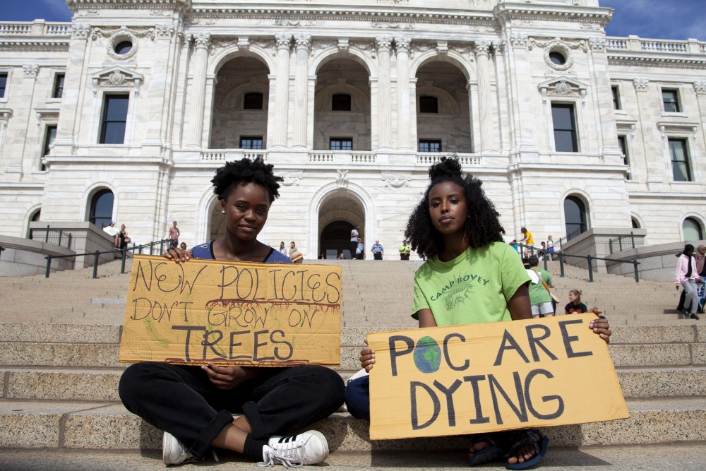 Protestors pose with signs outside the Minnesota State Capitol Building on Friday, Sept. 20, 2019. The Global Climate Strike drew crowds protesting the current state of environmental legislation.