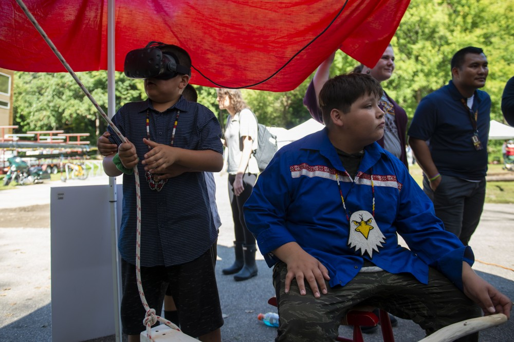 """Ganebik Johnson wears a virtual reality headset and attempts to steer a canoe at the """"Navigating Indigenous Futures"""" event on Thursday, Sept. 19, 2019."""