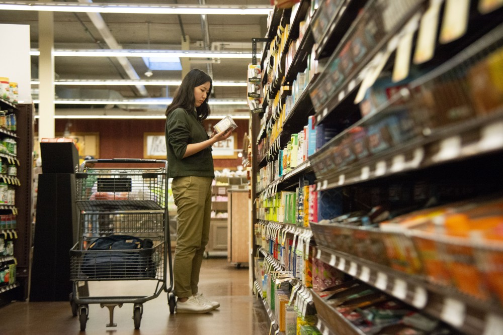 <p>Xuening Gao, a student from China studying Economics, shops for groceries at the Fresh Thyme in Prospect Park on Monday, Sept. 23. Due to currency exchange rates, living expenses and tuition fees have increased for Chinese students.</p>