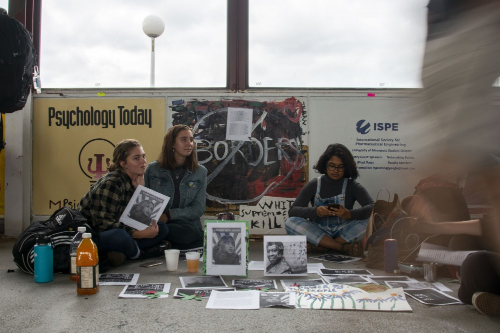 Student protestors sit in front of the College Republicans'