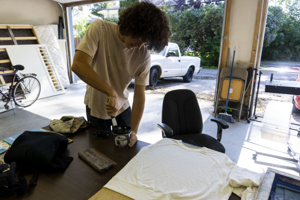 Drew Kinkade works on screen printing t-shirts for his clothing brand,