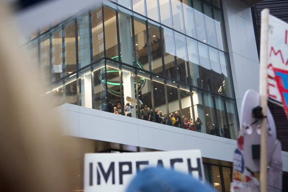 Attendees of a campaign rally held by President Trump in Minneapolis look down on demonstrators from the Target Center on Thursday, Oct. 10.