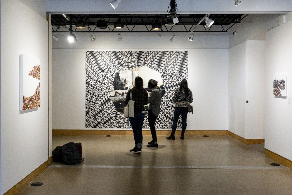 """Visitors interact with artwork on display at the """"Coffee with the Curator"""" event at All My Relations Arts Gallery on Wednesday, Oct. 9."""