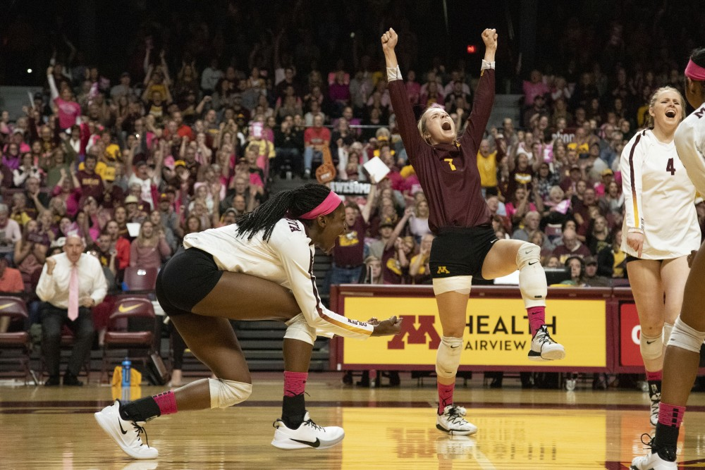 Adanna Rollins and CC McGraw celebrate a scored point at the Maturi Pavilion on Saturday, Oct. 19. The Gophers defeated Illinois three sets to one.