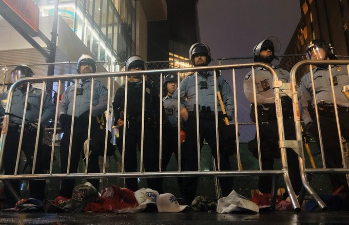 Minneapolis police officers stand outside a rally for President Donald Trump as protests grow increasingly hectic near Target Center on Thursday, Oct. 10.