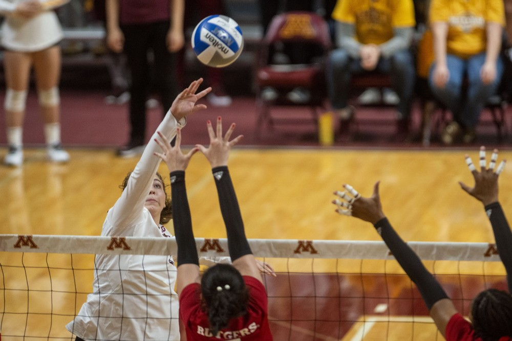 <p>Middle Blocker Regan Pittman jumps to spike the ball at the Matrui Pavilion on Saturday, Oct. 5. The Gophers defeated Rutgers three sets to one. </p>