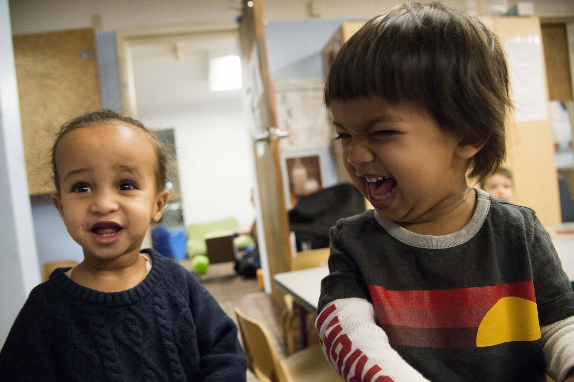 Taymia, 2, left, and Rishi, 2, right, laugh after looking at their photos at the Como Early Learning Center on Tuesday, Nov. 19.