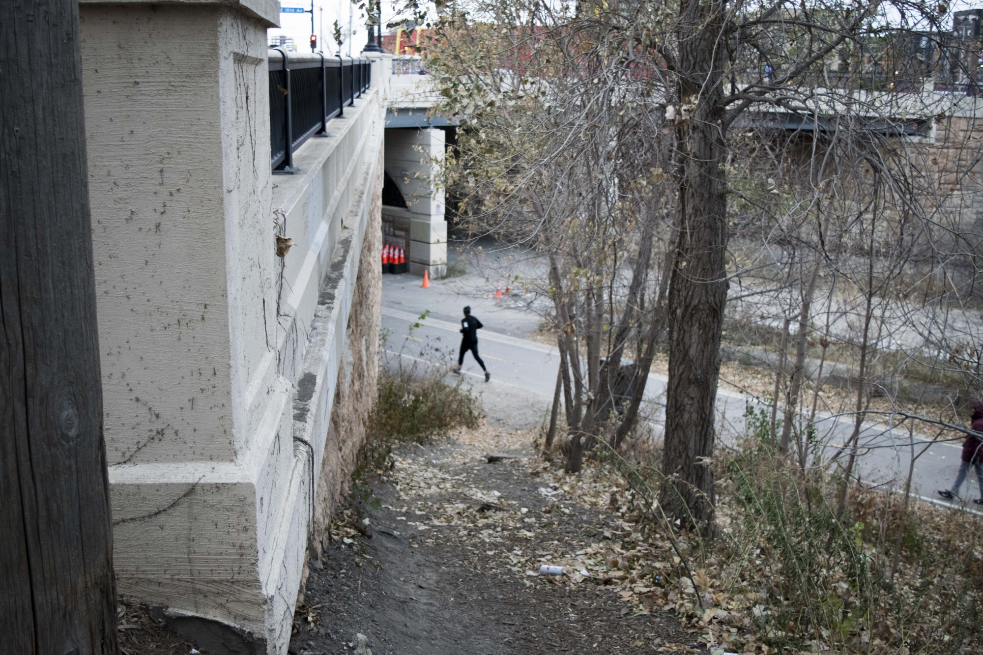 A runner passes the possible site of a new stairway connecting the Dinkytown Greenway to the intersection of Fourth Street Southeast and 15th Avenue Southeast on Tuesday, Nov. 12.