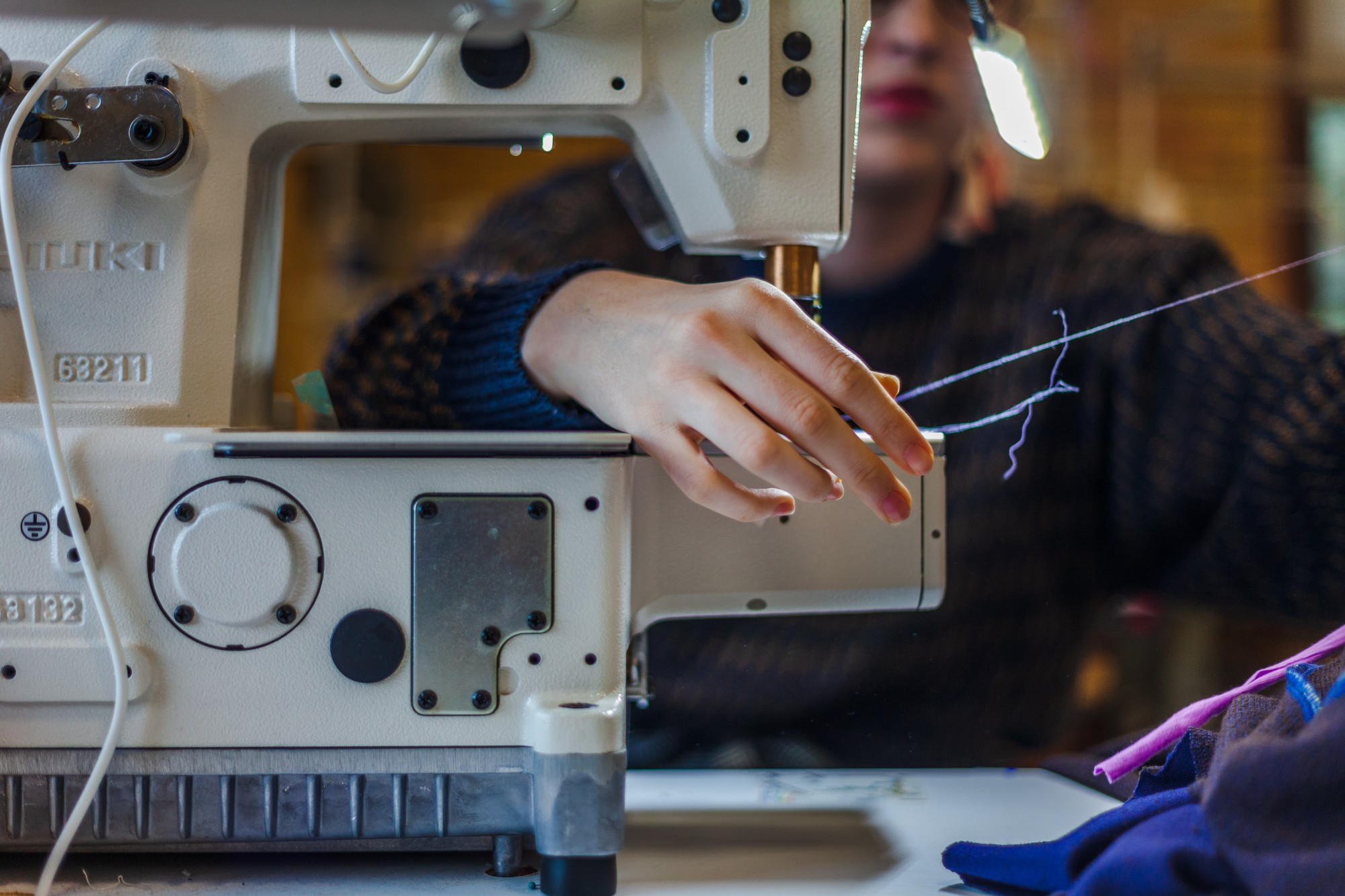 Britt, who is seen threading a sewing machine, has benefitted from the technical expertise she has gained while attending the University of Minnesota.