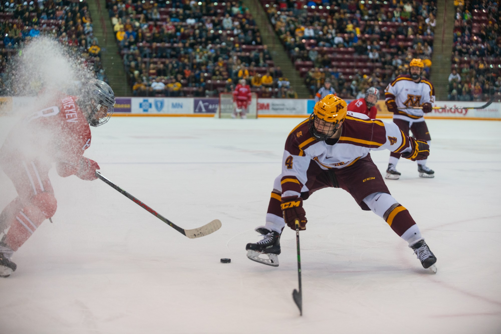 Gophers defender Ben Brinkman struggles for control over the puck at 3M Arena at Mariucci on Friday, Jan. 24. The Gophers went on to defeat Ohio State 6 to 3.