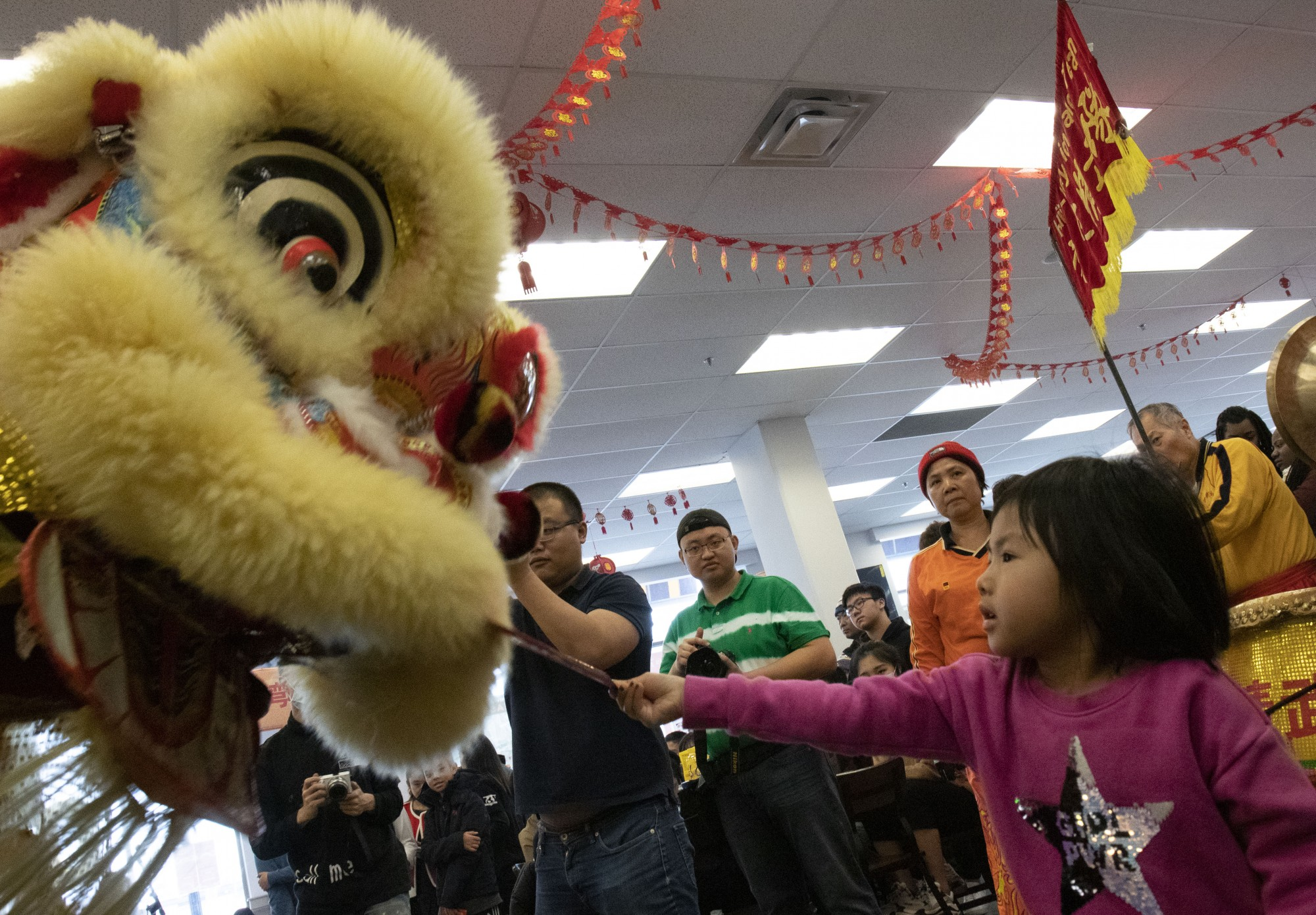"""Monica Tran """"feeds"""" the lion during the Lion Dance performed by Hu's Lucky Lion Dance Team while attending the Lunar New Year celebration at University Food Hall with her father Vu Tran on Sunday, Jan. 26. """"Feeding"""" the lion, either with friuts or with rewards for the lion troupe, is a tradition to bring prosperity and good luck in the coming year."""