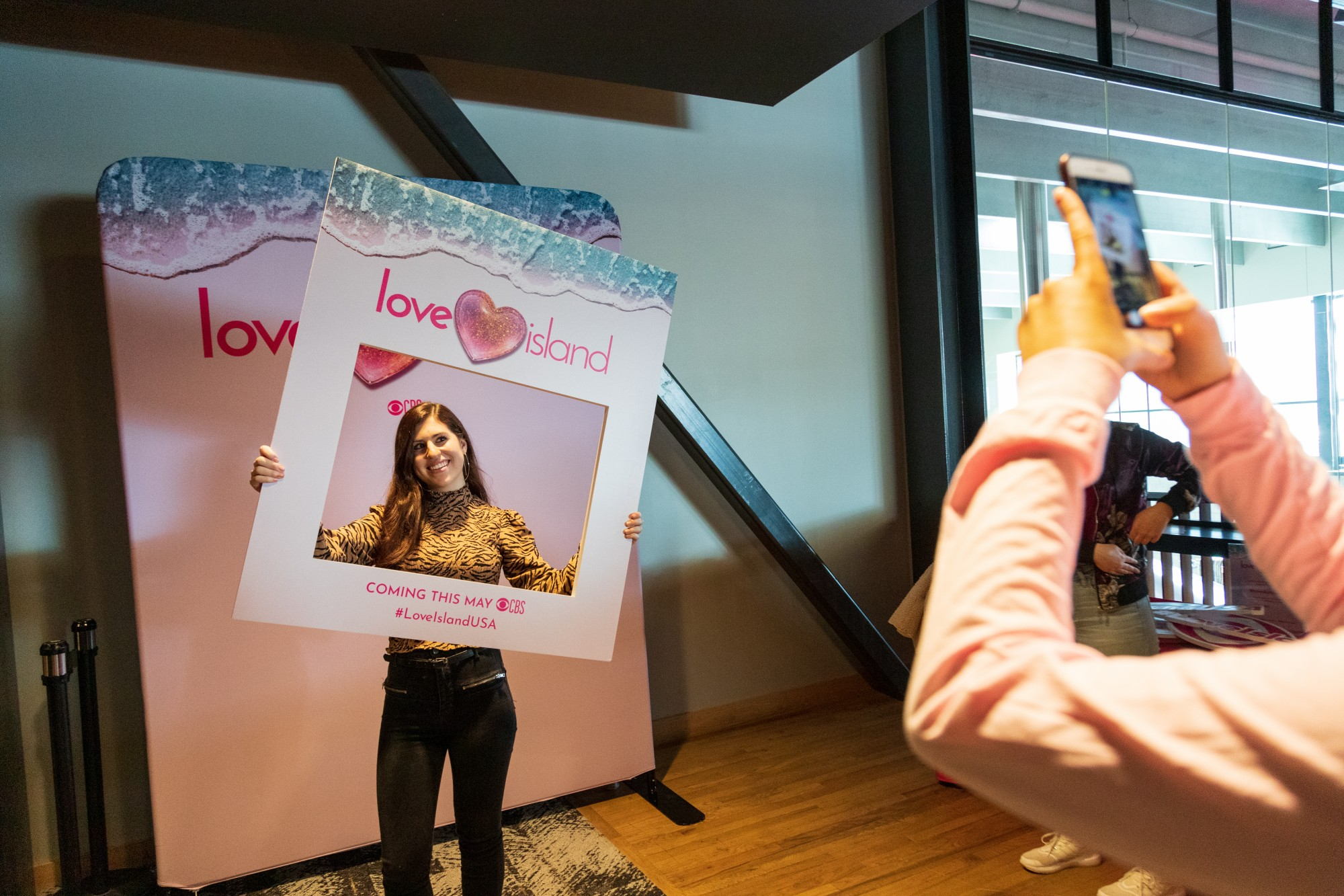 An attendee poses for a photo with Love Island USA props at an open casting call for the show's second season at Surly Brewing Company on Saturday, Feb. 15.
