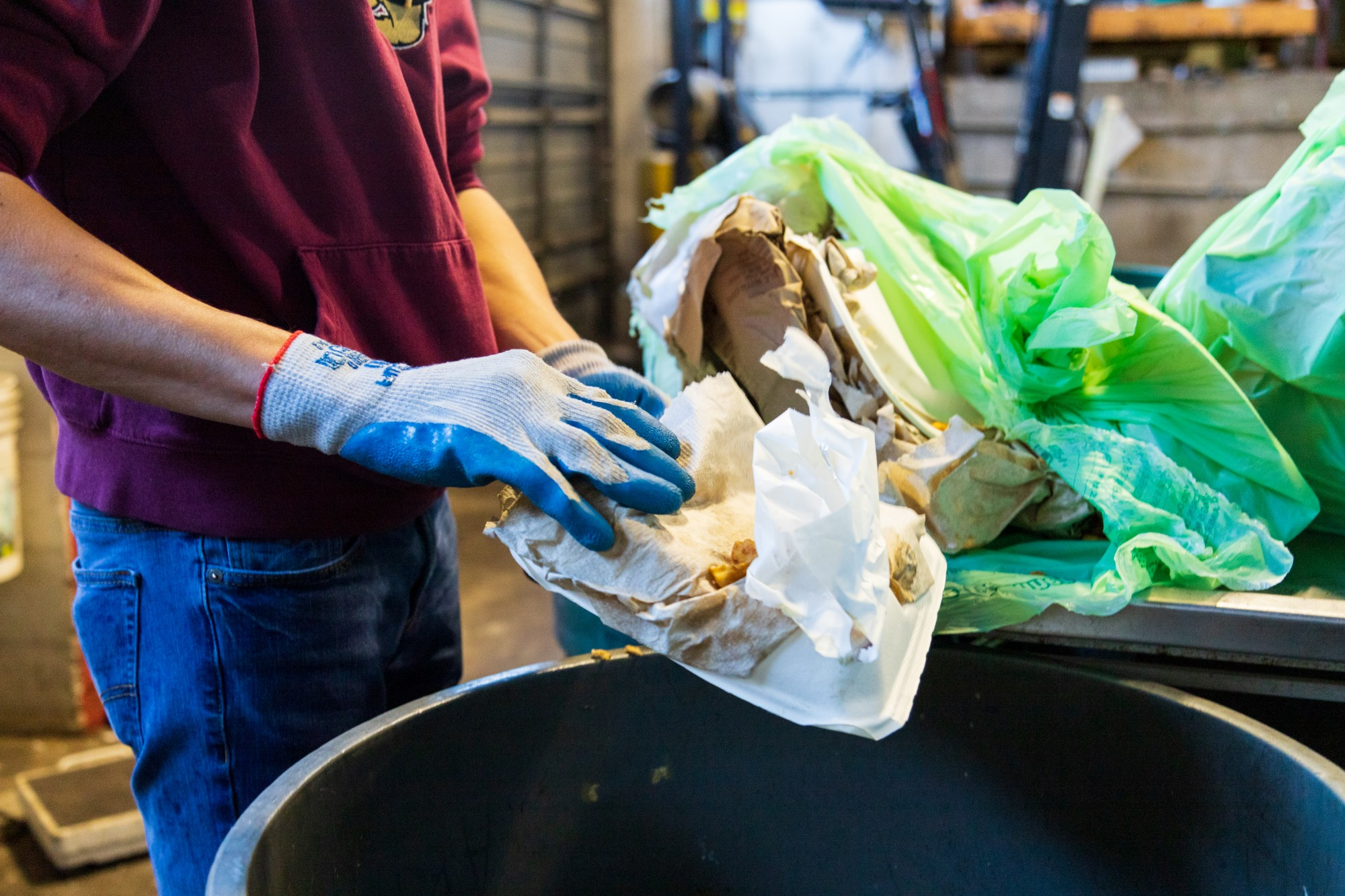 Student Worker Bailey Krolnika sorts through organics recycling from a University residence hall at Como recycling center on Wednesday, Feb. 19.