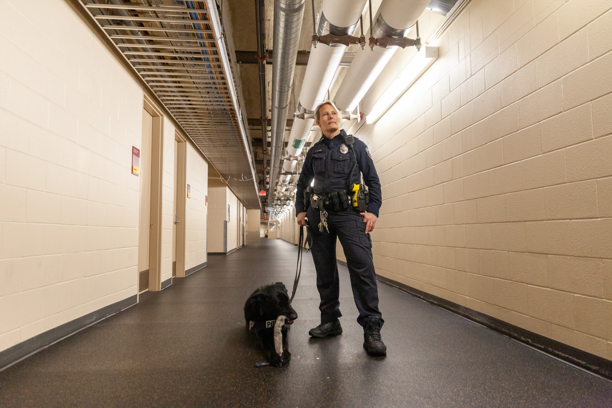 UMPD K-9 Patrol Officer Lara Bauer stands with her dual purpose canine Rio at TCF Bank Stadium on Tuesday, Feb. 25. Prior to serving as a dog handler, Bauer was a member of the University's mounted patrol unit, which was disbanded in 2012.