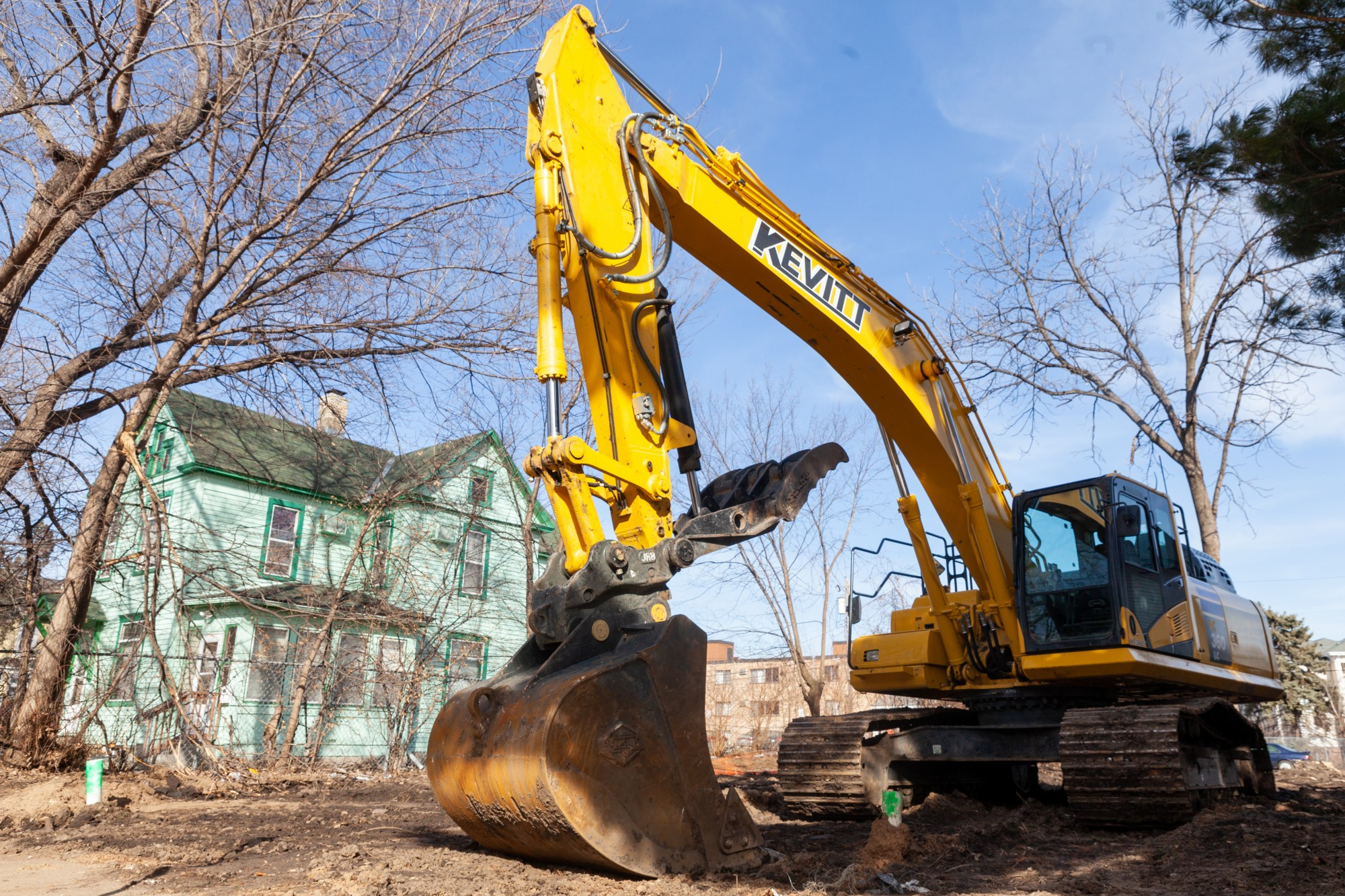 Construction equipment stands ready on an empty plot of land beside homes on Erie Street Southeast. on Friday, March 13. Several homes on the block are set to be demolished as part of a broad plan for the future clinical campus facility.