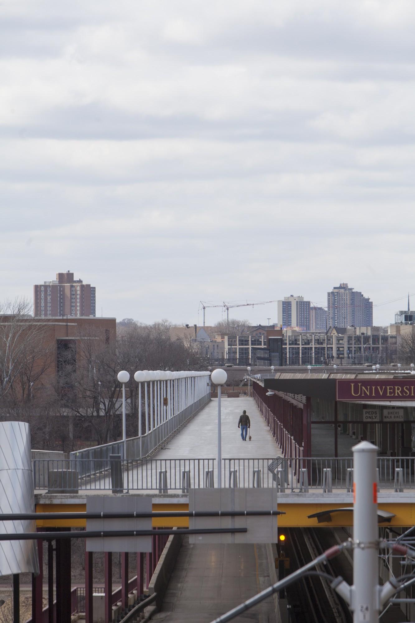 A man walks his dog along a quiet Washington Avenue bridge on Saturday, March 21.