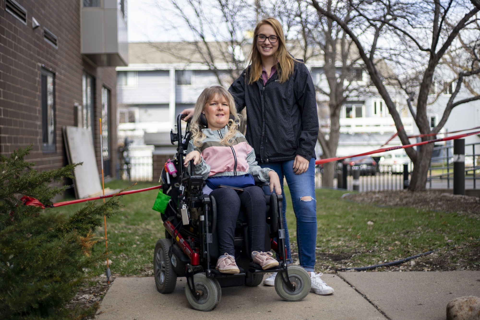 """Jen Onsum, left, and Paige Wolf, her personal care assistant pose for a portrait outside her apartment building on Wednesday, April 15. """"I have no choice but to trust that my PCAs are practicing social distancing and self-isolation,"""" said Onsum."""
