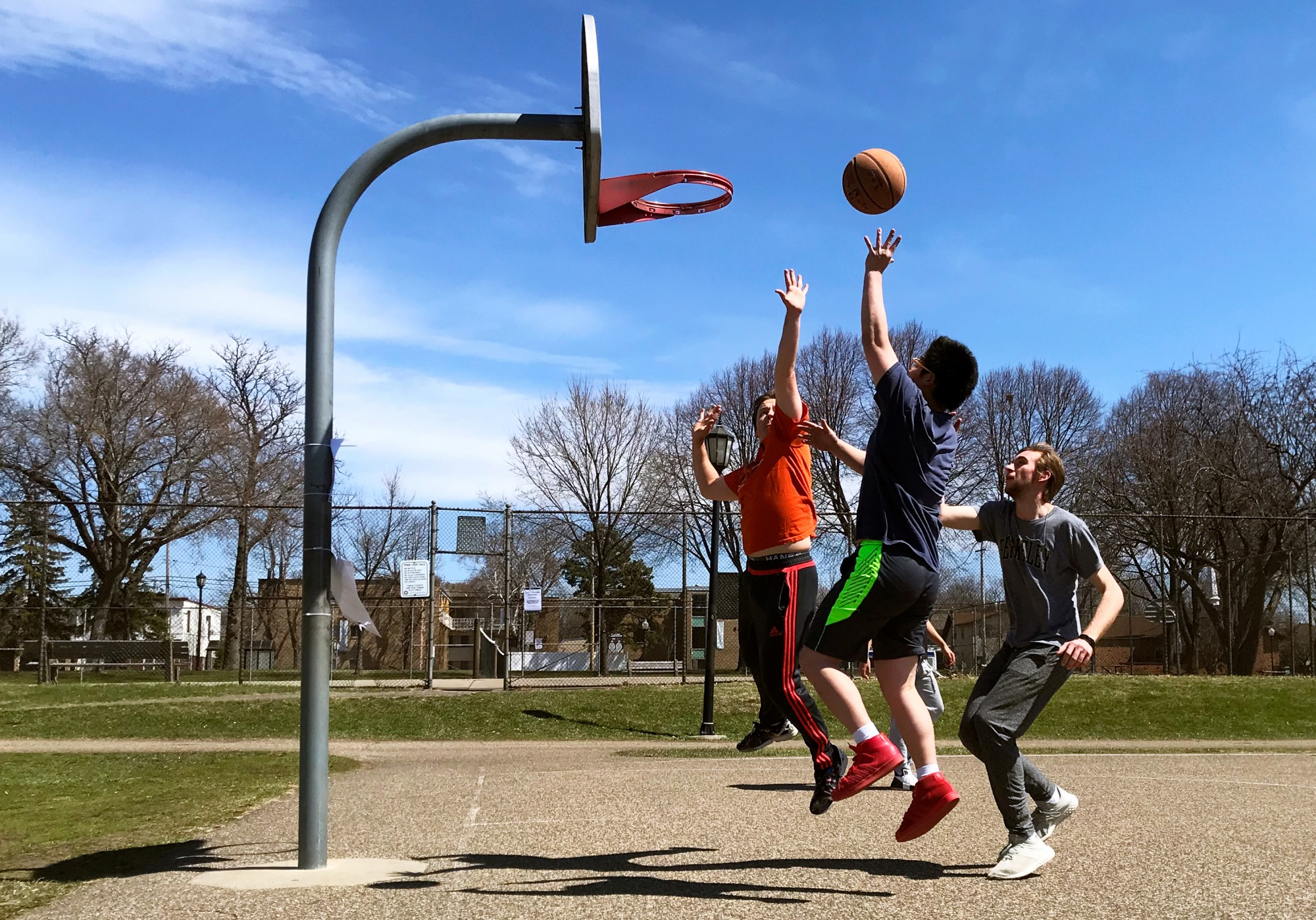 Roommates and University of Minnesota students from left, Harold Carpenter,  Wenxuan Li, Myles Mickens and Brandon Chan play a game of basketball in Van Cleve Park on Tuesday, April 21. The group relocated their frequent games after the hoops at Comstock Hall had the rims removed to prevent transmission of coronavirus.