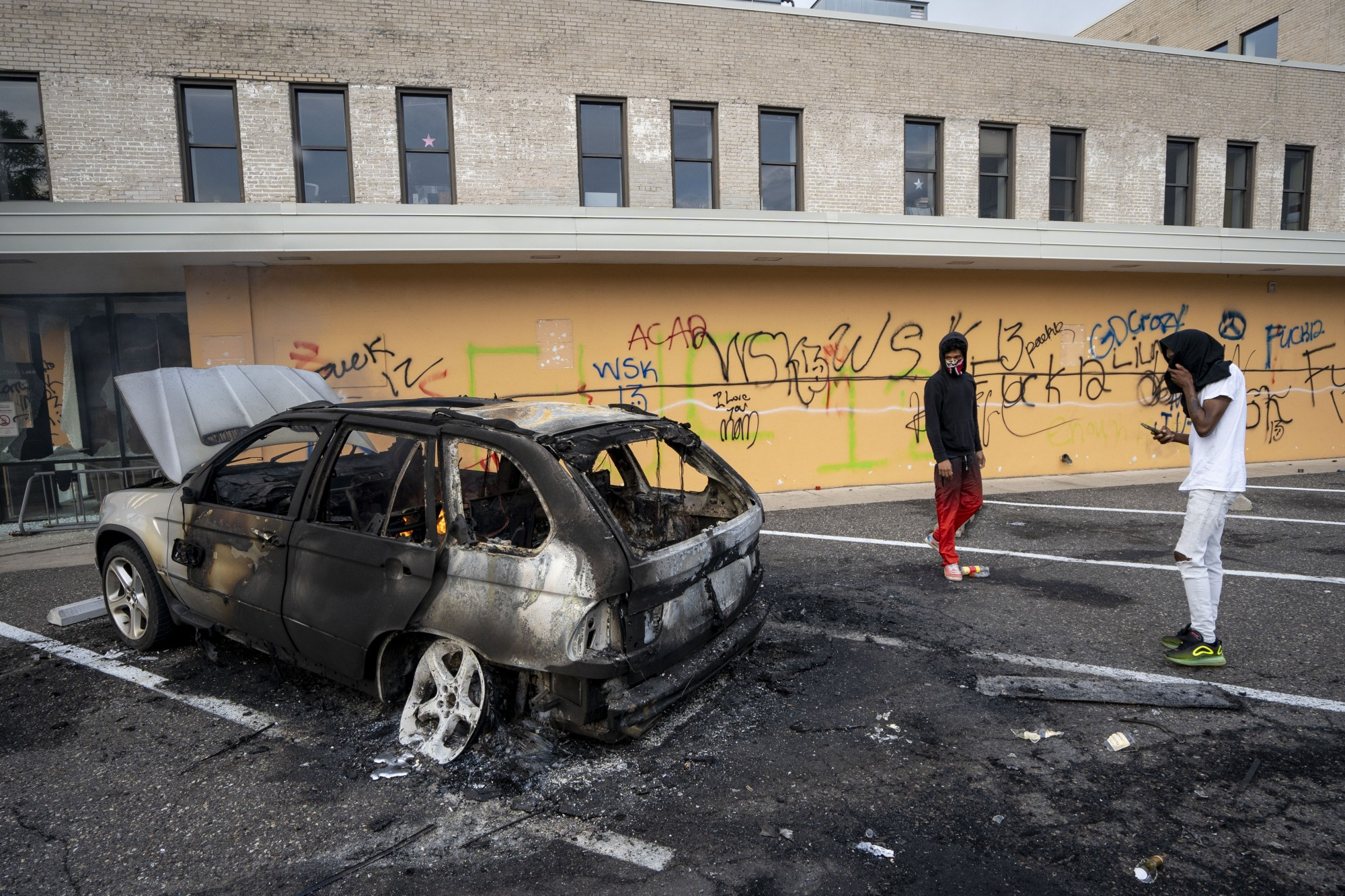 A burned-out car remains the morning after a second night of protests where dozens of businesses were vandalized near the Minneapolis Police 3rd Precinct on Thursday, May 28.