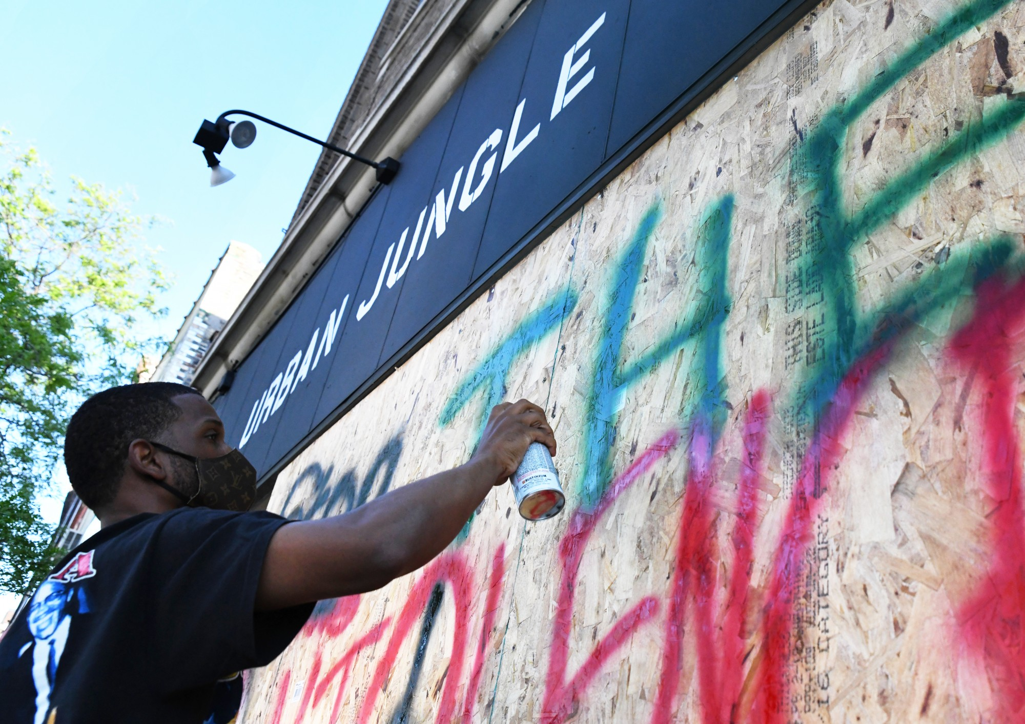 """Tommie Daye, owner of Urban Jungle, spray paints """"Stop the Violence"""" on his boarded-up shop window in the Cedar-Riverside neighborhood on Thursday, May 28."""